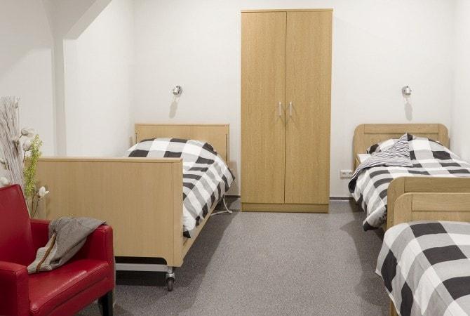 Slaapkamer met 3 bedden, stoel en kast groepsaccommodatie De Leilinde